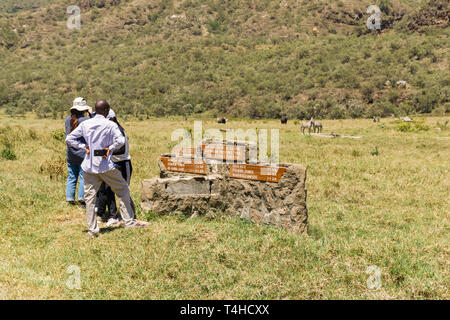 Tourists standing by stone road sign looking at wildlife, Hells Gate National Park, Kenya - Stock Image