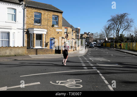 Rear view of a young woman wearing lycra running along Pulross Rd at the corner of Dalyell Road houses in Brixton South London England UK KATHY DEWITT - Stock Image