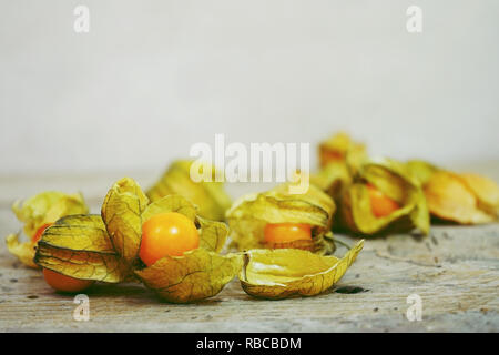Beautiful and elegant macro close-up of a lot orange tasty fruit named physalis from Peru, South America, over wooden tables - Stock Image