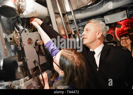 PITTSBURGH, Pa. (Mar. 14, 2019) Senior Chief Dave Jackson, from Denver, Colorado, and his daughter show visitors onboard the USS Requin (SS 481) how to use the dive alarm. Jackson is stationed on the nuclear-powered Los Angeles-class, fast-attack submarine USS Pittsburgh (SSN 720) and visited the Requin at the Carnegie Science Center with other crewmembers. Pittsburgh crewmembers are participating in various events around Pittsburgh to bring awareness to the U.S. Navy's mission. The Navy's fast-attack submarines are designed to seek and destroy enemy submarines and surface ships; deliver missi - Stock Image