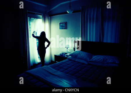 Woman looks out of french doors in bedroom. - Stock Image