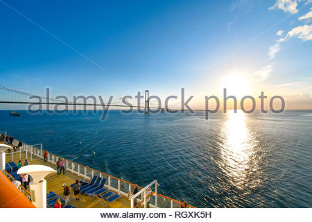 Tourists wait and take photos from upper deck as a cruise ship passes under the Oresund Bridge spanning the strait between Sweden and Denmark - Stock Image
