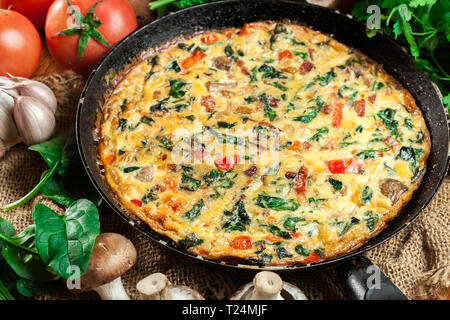 Frittata made of eggs, mushrooms and spinach on a frying pan. Italian cuisine - Stock Image