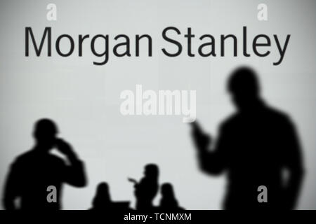 The Morgan Stanley logo is seen on an LED screen in the background while a silhouetted person uses a smartphone in the foreground (Editorial use only) - Stock Image