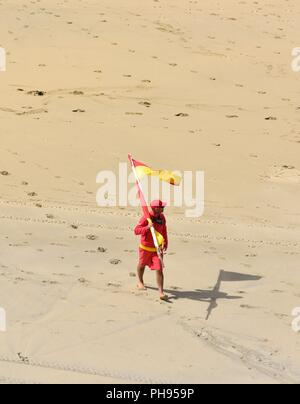 RNLI lifeguard on duty carrying a red and yellow flag across the beach,Riviere Towans beach,Riviere Towans beach, Phillack, Hayle,cornwall,England,UK - Stock Image