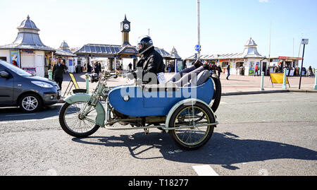 Brighton, UK. 24th March 2019. Frank Mace on his 1912 Clyno motorcycle with an interestingly seated passenger in the  sidecar arrive in Brighton as they take part in the 80th Anniversary Pioneer Run for pre 2015 veteran motorcycles . The run organised by the Sunbeam Motor Cycle Club begins on the Epsom Downs in Surrey and finishes on Madeira Drive on Brighton seafront Credit: Simon Dack/Alamy Live News - Stock Image