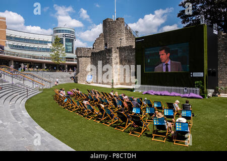 Southampton, UK.  11th July 2017 West Quay Southampton. UK Weather Spectators enjoying the sunshine whilst watching Wimbledon tennis on a large TV screen. Credit Paul Chambers Alamy/Live News - Stock Image