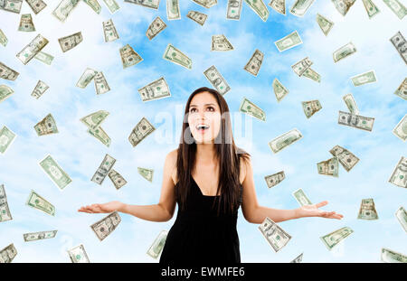 Stock image of woman standing with open arms amidst falling money - Stock Image
