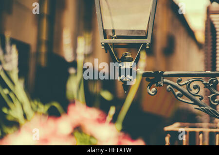 Fragment of old black glass and metal toreutic lantern with blurred balcony and narrow street behind and pink flowers - Stock Image