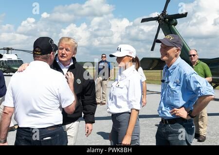 Panama City, Florida, USA. 15th Oct 2018. U.S President Donald Trump speaks with a local resident after touring damage in the aftermath of Hurricane Michael at Northwest Beaches International Airport October 15, 2018 in Panama City, Florida. Standing with the president from left to right are: Local resident, President Donald Trump, First Lady Melania Trump and Florida Gov. Rick Scott. Credit: Planetpix/Alamy Live News - Stock Image