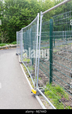 Temporary wire mesh fencing separating a surfaced footpath from a construction site. - Stock Image