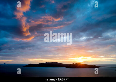 Spectacular sunset over the Aegean volcanic island caldera of Santorini with striking blue sky and orange clouds - Stock Image