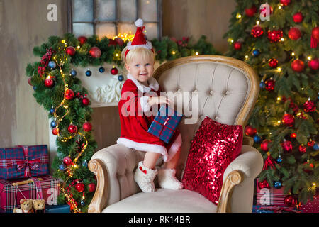 Merry Christmas and Happy Holidays Cute little child girl is decorating the Christmas tree indoors - Stock Image