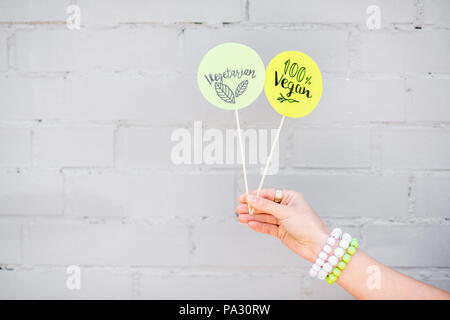 Holding stickers with healthy food slogans on the gray wall background - Stock Image