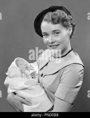 1950s PORTRAIT SMILING YOUNG WOMAN MOTHER WEARING BERET HAT LOOKING AT CAMERA HOLDING INFANT BABY SON IN ARMS  - b5169 HAR001 HARS URBAN MOTHERS OLD TIME NOSTALGIA HUGGING OLD FASHION 1 JUVENILE STYLE YOUNG ADULT INFANT EMBRACE SONS PLEASED JOY LIFESTYLE CELEBRATION FEMALES STUDIO SHOT HEALTHINESS HOME LIFE HALF-LENGTH HUG LADIES PERSONS CARING MALES EMBRACING B&W EYE CONTACT HAPPINESS TIGHT CHEERFUL PRIDE IN SMILES CONNECTION JOYFUL STYLISH BABY BOY BERET JUVENILES MOMS TOGETHERNESS YOUNG ADULT WOMAN BLACK AND WHITE CAUCASIAN ETHNICITY HAR001 OLD FASHIONED - Stock Image