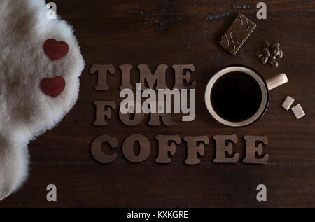 beautiful flat lay of mug with coffee, sheepskin, chocolate and text time for coffee, on rustic wooden background - Stock Image