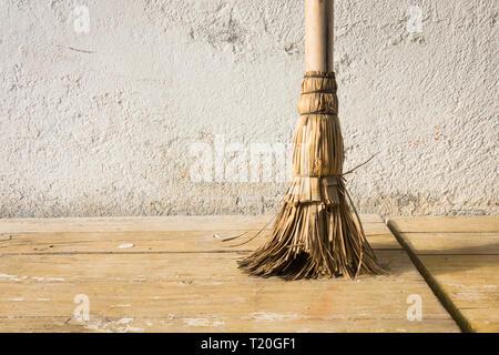Vintage old used broom against white wall. - Stock Image