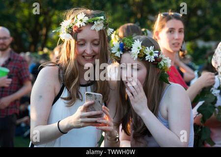 Two women looking at a cellphone with amusement and astonishment during the annual Swedish Midsummer Festival in Battery Park City's Wagner Park. - Stock Image