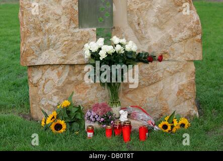 White roses, candles and sun flowers are laid to a memorial stone during a oecumenical service in Lathen, Germany, - Stock Image