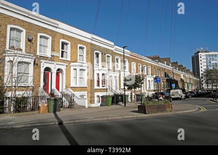 Row of terraced housing on Bellefirelds Road in Brixton with parked cars and rubbish bins outside houses, South London England UK  KATHY DEWITT - Stock Image
