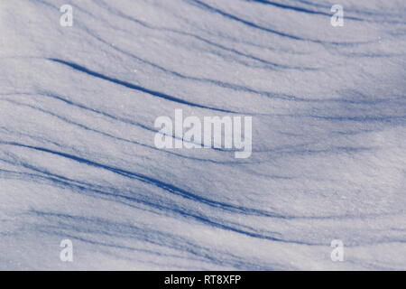 The wind has formed patterns in the snow covering a frozen lake. - Stock Image