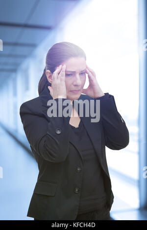 Middle aged woman with chronic pain syndrome fibromyalgia suffering from an acute migraine attack at her office - Stock Image