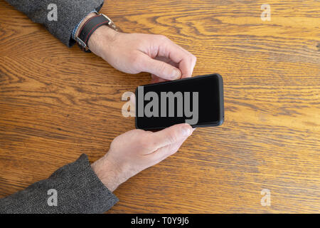 Man holding a smart phone in hands while waiting to be served at restaurant. Phone with empty black curved screen - Stock Image