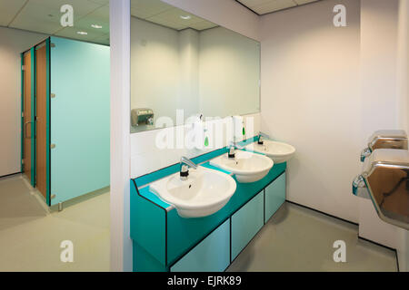 Wash basins, hand dryers and toilet cubicals of modern restroom - Stock Image