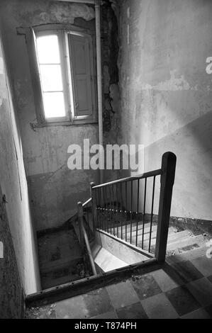 Interior stairs in ruined facilities at the abandoned Canfranc International railway station (Canfranc, Pyrenees, Huesca, Aragon, Spain). B&W version - Stock Image