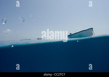 A split shot, with half underwater and half showing a row of small boats tied up behind a larger boat on a calm - Stock Image