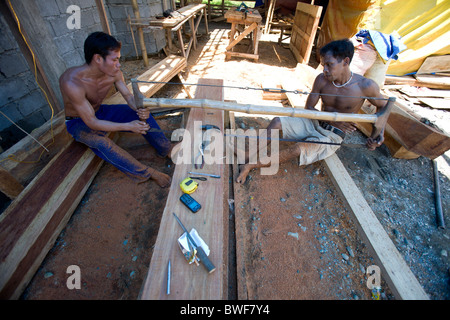 Filipino laborers team saw a bulk piece of narra wood into planks in Mansalay, Oriental Mindoro, Philippines. - Stock Image
