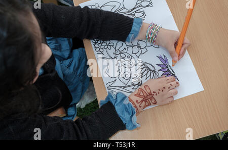 February 22, 2019 - Abu Dhabi, UAE: A little girl with Henna tattoo on her hand coloring flowers on paper - Stock Image