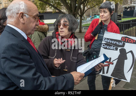 London, UK. 19th Dec, 2018. Maggie Zolobuaijluk of DPAC shows Ealing Southall Labour MP Virendra Sharma her dossier of some deaths caused by the cuts at the protest in support of the parliamentary debate due later in the day on the cumulative impact of the cuts on the lives of disabled people. They say the government cuts and changes in benefits, along with inappropriate benefit sanctions, have had a disproportionate effect on disabled people, resulting in great hardship, denying people their rights and many deaths. Credit: Peter Marshall/Alamy Live News - Stock Image