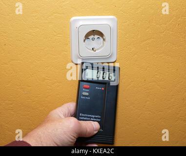 Testing electromagnetic radiation level of indoor power line socket - Stock Image