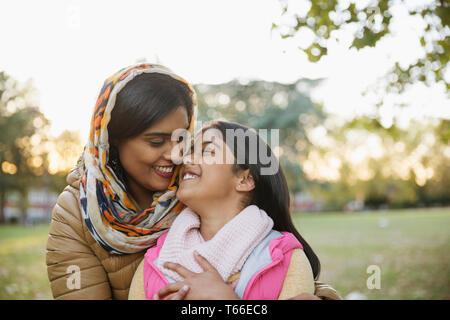 Affectionate, happy Muslim mother in hijab hugging daughter in autumn park - Stock Image