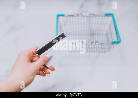 woman's hand holding payment card in front of empty shopping basket, concept of shopping budget - Stock Image