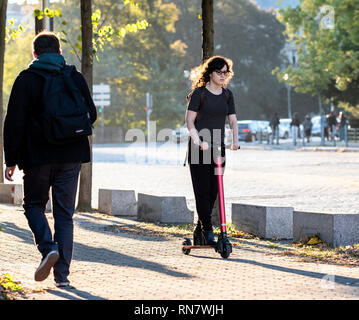 Strasbourg, Alsace, France, young woman riding her dockless electric scooter on pavement, - Stock Image