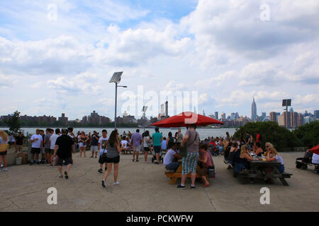 People eating their snacks at Smorgasburg in Williamsburg, Brooklyn on JULY 8th, 2017 in New York, USA. (Photo by Wojciech Migda) - Stock Image