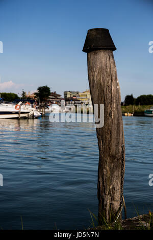 Pile in the water with yachts and boats moored in the dock in the background - Stock Image