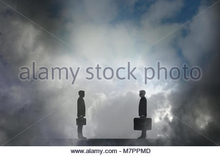 Businessman with small briefcase face to face with businessman carrying large briefcase - Stock Image