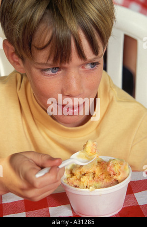 9+ Caucasian boy eats ice cream from cup - Stock Image
