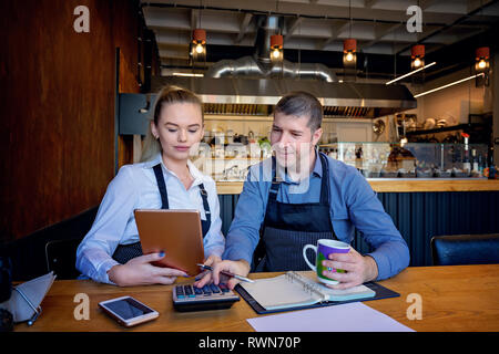 Small family restaurant owners checking monthly reports. Man and woman wearing apron doing accounts for their small restaurant. - Stock Image