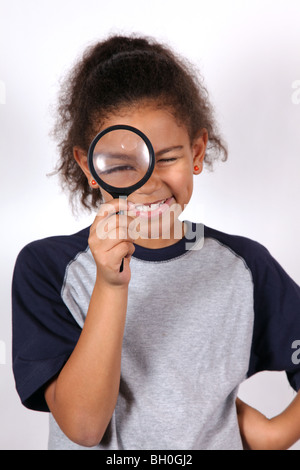 African-American girl looking through a magnifying glass - Stock Image