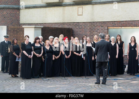 Portsmouth, UK. 15th Aug, 2015. Portsmouth Military Wives Choir sing 'On My Own' during the wreath laying - Stock Image