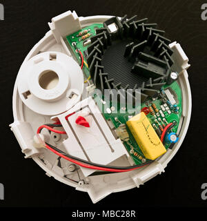 Components inside an optical smoke detector showing the black optical smoke detection chamber where light scattered by smoke particles is detected. - Stock Image