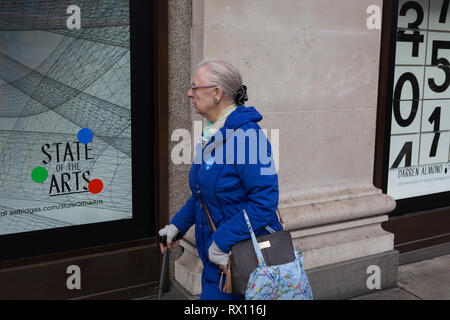 A shopper walks past a window display that features numbers - part of a design theme called 'State of the Arts', at the Selfridges department store on Oxford Street, on 4th March 2019, in London England. Darren Almond's piece 'Chance Encounter 004', consists of a grid formed from rectangular panels, featuring fragmented numbers that appear to scroll across the surface.  State of the Arts is a gallery of works by nine crtically-acclaimed artists in Selfridges windows to celebrate the power of public art. - Stock Image