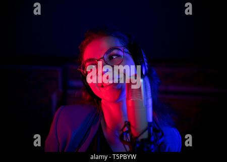 A young smiling woman in glasses singing by the microphone in neon lighting - Stock Image