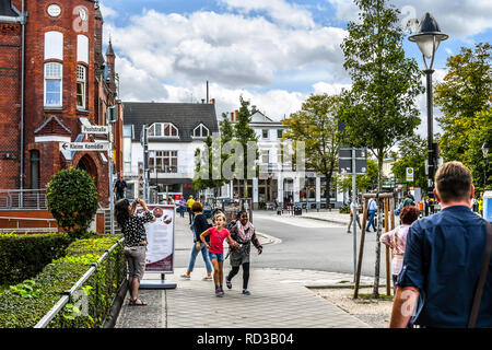 A young black girl and her young white friend walk hand in hand on a picturesque street in Warnemunde, Germany - Stock Image