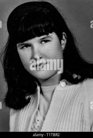 1970s indoor studio portrait of a young woman in black and white taken with 35mm film - Stock Image