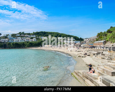 6 June 2018: Looe, Cornwall, UK - Visitors enjoying the beach on a warm and sunny spring day. - Stock Image